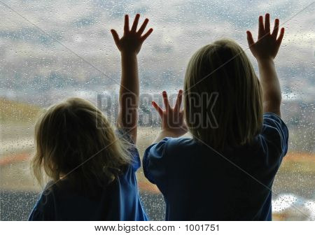 little girl standing by window with raindrops on it on a rainy day stock photo