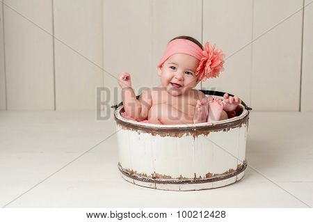 Six Month Old Baby Girl Sitting in a Vintage Wooden Bucket. She is Laughing and Wearing a Large Peach Colored Flower Headband. stock photo