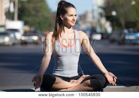 Yoga in the city: smiling beautiful young fit woman meditating breathing sitting in Half Lotus Posture on the street with busy road traffic on summer day Ardha Padmasana stock photo