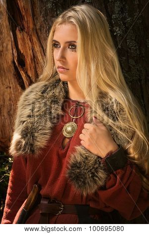 Scandinavian girl with runic signs on a forest background stock photo