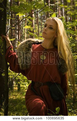 Scandinavian girl with runic signs on a forest background