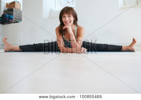 Happy woman doing wide angle seated forward bend yoga at gym. Fitness female practicing Upavistha Konasana yoga. Caucasian woman doing the splits. stock photo
