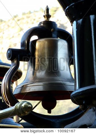 Antique hand operated brass bell on vintage narrow gauge steam engine ** Note: Slight blurriness, best at smaller sizes stock photo