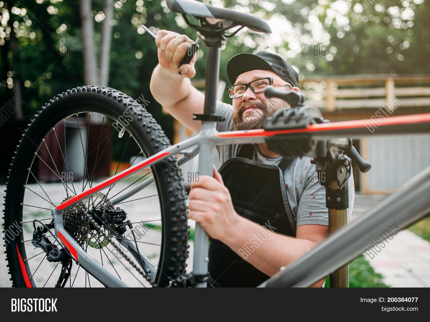 adjust,bearded,bicycle,bicycling,bike,biker,biking,broken,business,chain,cycle,cyclist,equipment,fix,fixing,gear,glasses,hand,job,maintenance,male,man,master,mechanic,occupation,outdoor,person,profession,professional,repair,repairer,repairman,seat,service,serviceman,shop,sport,store,technician,tire,tool,tyre,wheel,work,worker,workshop,wrench