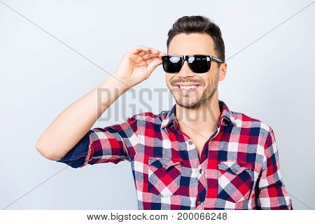 So cool and cheerful! Happy young brunet guy with stubble on vacation in a stylish sun protective spectacles wearing casual checkered shirt holding his glasses stock photo
