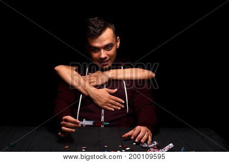 A close-up of a guy with a drug addiction on a black background. Drug-dependent with a syringe. Liquid ecstasy in a syringe. Hands keeping a boy from the drug injection. Drug concept. Copy space. stock photo