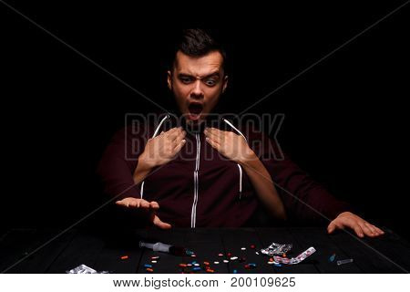 A weak man taking a syringe next to various addictive drugs on a black table. Woman's hands holding a drug addict from the back on the black background. Morphine, LSD, meth, marijuana addiction. stock photo