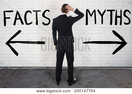 Rear view of confused businessman looking at arrow signs below facts and myths text