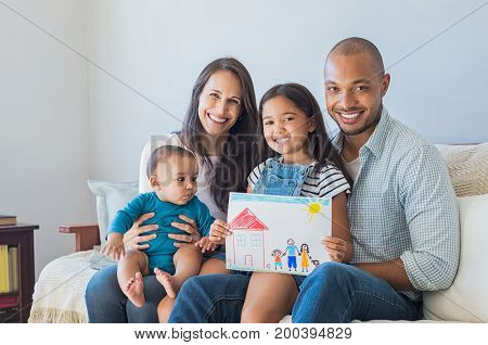 Daughter showing drawing of a happy family in new house. Cute infant looking at colorful drawing of