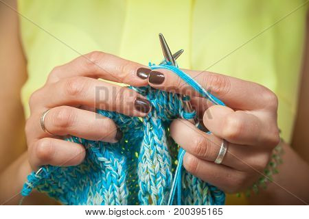Close-up of a woman knits with knitting needles from natural woolen threads a white and blue sweater a woman shows how to knit correctly stock photo