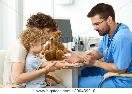 Portrait of young mother with little kid at doctors office, woman holding childs arm when taking blood test in doctors office