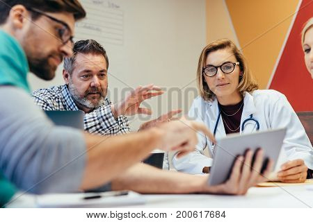 Group of healthcare workers with digital tablet meeting in hospital boardroom. Medical staff during morning briefing. stock photo