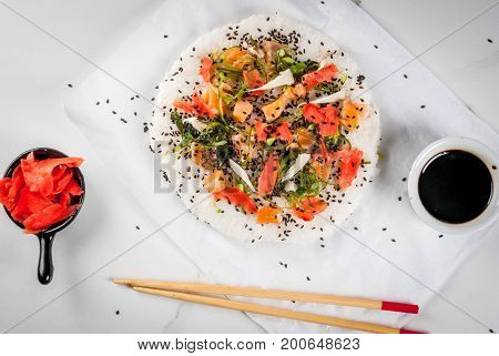 Trend hybrid food. Japanese Asian cuisine. Sushi pizza with salmon hayashi wakame daikon pickled ginger red caviar. On a white marble table with chopsticks and soy sauce. Copy space top view stock photo