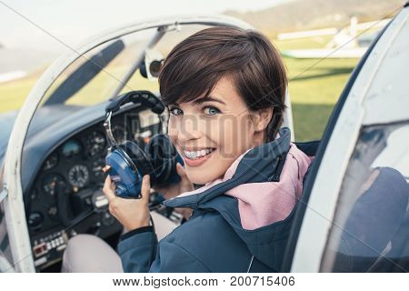 Smiling female pilot in the light aircraft cockpit she is holding aviator headset and looking at camera stock photo
