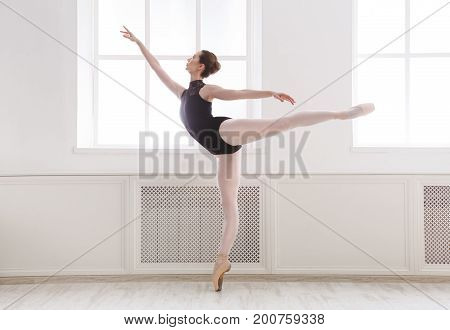 Young graceful ballerina in black at ballet class making arabesque. Classical dancer in light hall practicing positions near large window, side view, copy space