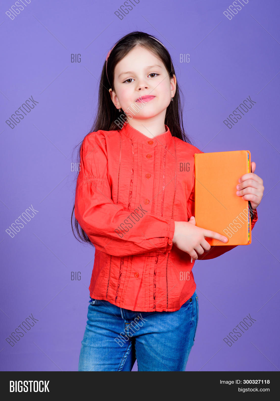 Confident In Her Knowledge. Adorable Small Girl Holding Book With Orange Cover. Cute Little Child Wi