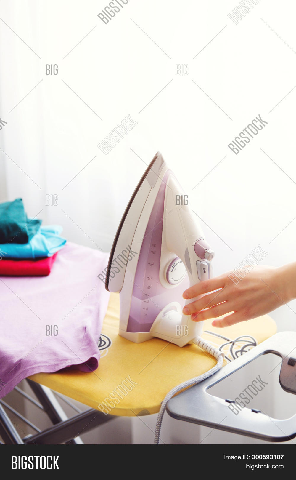 The Woman The Housewife Irons Clothes At Home. On The Ironing Board Iron And Purple T-shirt, As Well