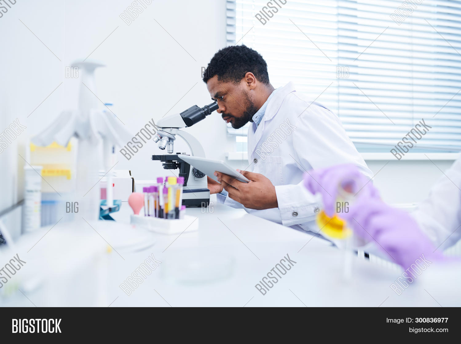 Concentrated Handsome Black Male Lab Technician With Beard Sitting At Table And Using Microscope Whi