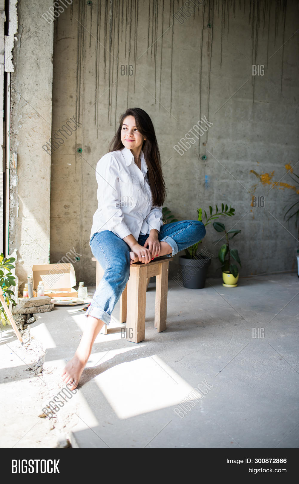 Beautiful Young Lady Artist In White Shirt Sitting Barefoot In Her Bohemian Artistic Studio Loft