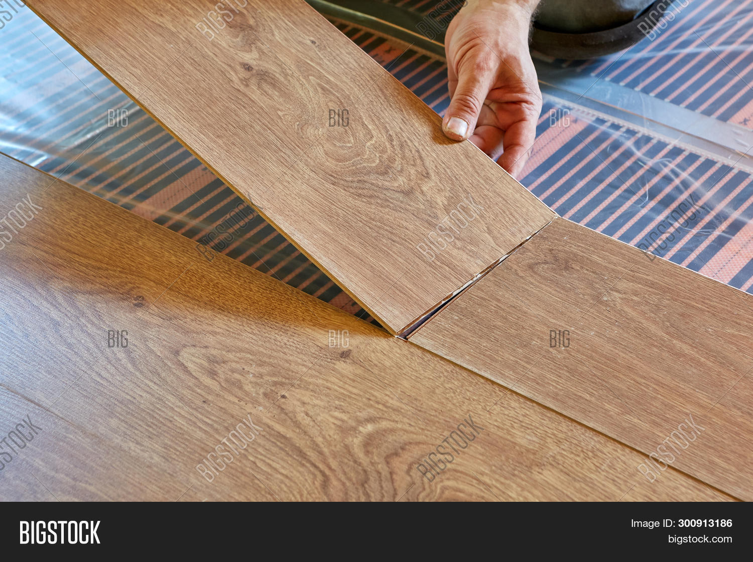 Laminate flooring. Male repairman is laying panel of  laminate floor  on a heat-insulated floor. Ele