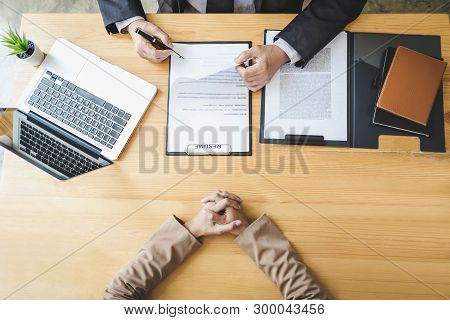 Interviewer or Board reading a resume during a job interview, Employer interviewing a young female job seeker for recruitment talking in modern office, employment and recruitment concept. stock photo