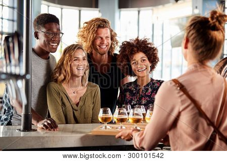 Waitress Serving Group Of Friends Beer Tasting In Bar stock photo