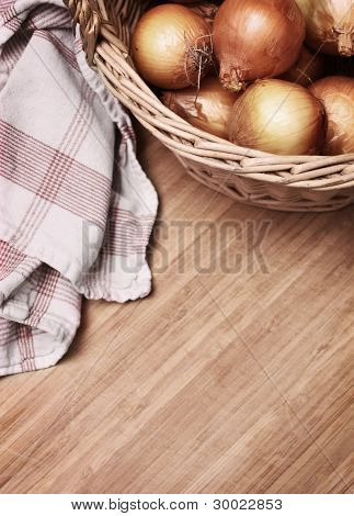onions in a basket on wooden background with towel stock photo