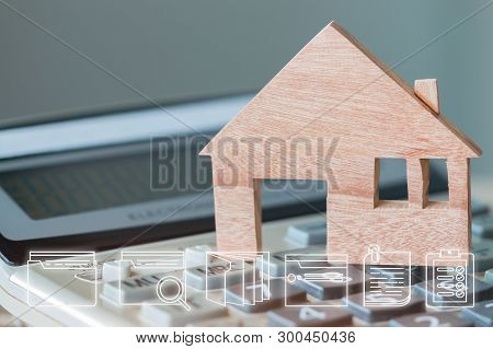 Wooden house model on calculator. Ideas for property real estate mortgage loan or investment with digital document file marketing icons. Concept of planing management for agreement to buy new home stock photo