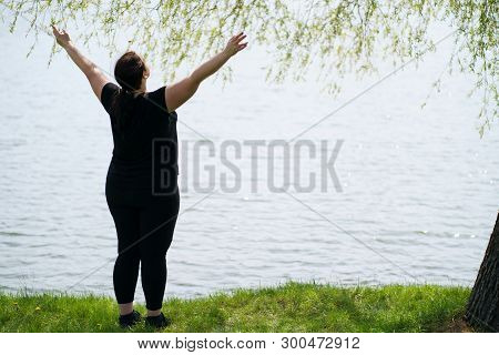 Body positive, success, freedom, happiness, confidence, self esteem. Overweight woman rising hands to the sky. Obesity and outdoor activity stock photo
