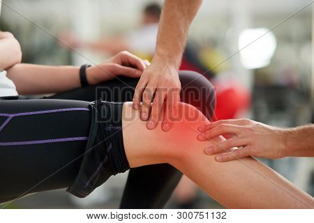 Muscle cramp during workout. Male hands helping relieve pain in female injured leg. Sport accident concept. stock photo