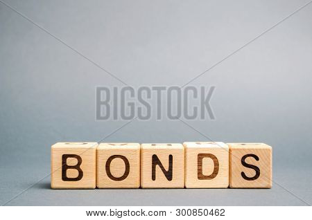 Wooden blocks with the word Bonds. A bond is a security that indicates that the investor has provided a loan to the issuer. Equivalent loan. Unsecured and secured bonds stock photo
