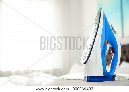 Modern electric iron on board indoors, space for text. Household appliance stock photo