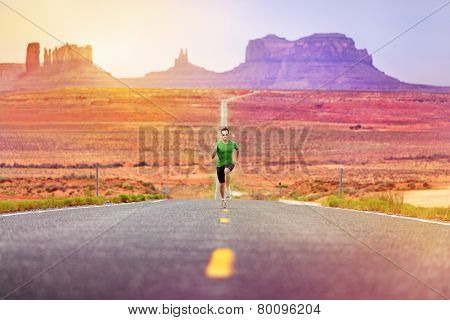 Runner man athlete running sprinting on road by Monument Valley. Concept with sprinter fast training