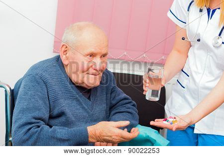 Nursing home assistant giving daily treatment to patient with Alzheimer's disease. stock photo