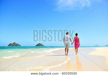 Beach honeymoon couple holding hands walking on white sand beach. Newlyweds happy in love relaxing o