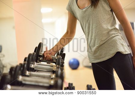 Gym woman strength training lifting dumbbell weights getting ready for exercise workout. Female fitn