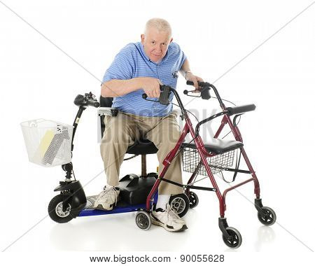 A senior man transferring from his electric scooter to his wheeling walker.  On a white background. stock photo