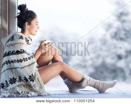Young beautiful happy brunette woman drinking cup of coffee wearing knitted nordic print poncho sitt