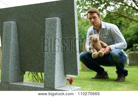 Father Placing Teddy Bear On Child's Grave In Cemetery stock photo