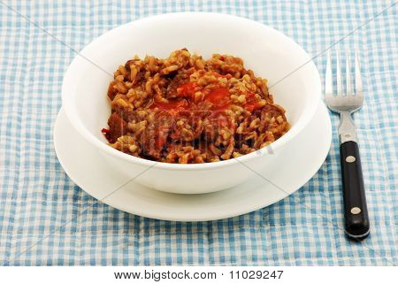 White bowl filled with a Cajun Cuisine favorite-red beans rice and chunks of sausage all topped with coating of spicy Louisiana Hot Sauce. All setting on blue gingham place mat with old fashioned fork. stock photo