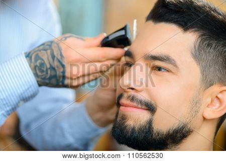 Happy client. Close up of pleasant smiling bearded man sitting in the barber shop while professional hairdresser cutting his hair stock photo