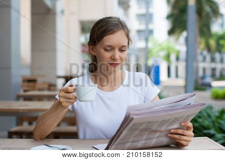 Closeup portrait of content young beautiful woman drinking coffee and reading newspaper at cafe table outdoors with street view in background. Front view.