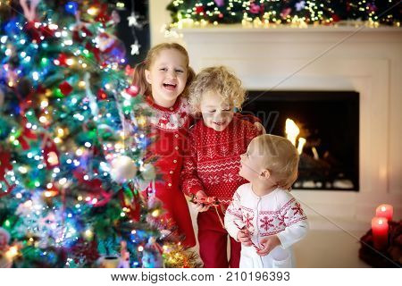 Children at Christmas tree and fireplace on Xmas eve. Family with kids celebrating Christmas at home. Boy and girl in matching sweater decorating xmas tree and opening presents. Holiday gifts for kid. stock photo