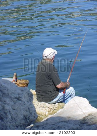 Lone elderly man fishing from the rocks by the blue sea on the French Riviera on a sunny summer day stock photo