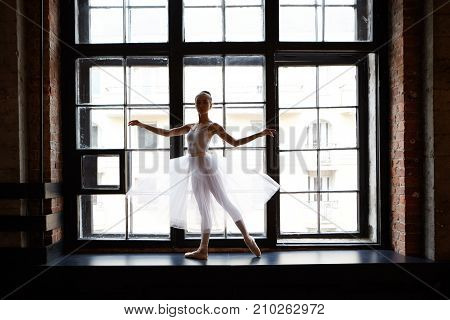 Full lenght picture of female classical ballet dancer in white tutu dancing in ballet studio standing on wide windowsill and looking at camera. People profession hobby and occupation concept