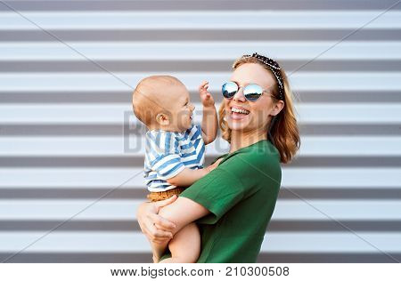 Young woman with a baby boy standing against the wall. Beautiful mother holding her son in arms. stock photo