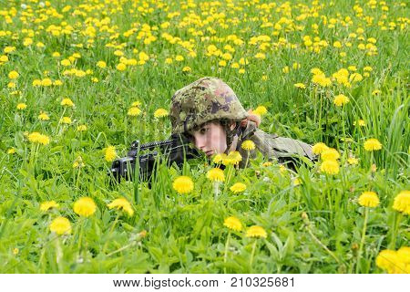 Portrait of armed woman with camouflage. Young female soldier observe with firearm. Child soldier with gun in war green goutweed and yellow dandelions background. Military army people concept stock photo