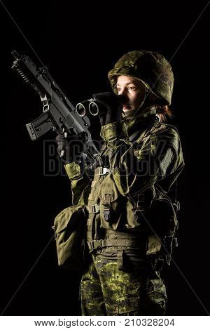 Portrait of armed woman with camouflage. Young female soldier observe with binoculars. Child soldier with gun in war black background. Military army people concept stock photo