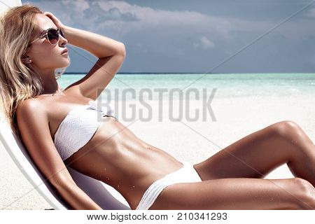 fashion photo of beautiful tanned woman with blond hair in elegant white bikini relaxing on white chair in tropical island with perfect beach.