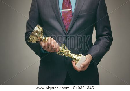 Awards ceremony. Business success. Best worker. The winner man in suit holds in front of him the award golden cup trophy in his hands.